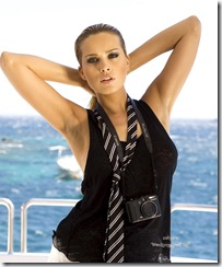 Attitude sexy de la top modèle tchèque Petra NEMCOVA, nouvelle égérie de la marque de luxe de Grisogono, les bras derrière la tête, les cheveux mouillés coiffés en arrière, portant un haut sans manche et une cravate défaite, un appareil photo autour du cou, sur le pont d'un bateau, découvrant la mer Egée au large de Mykonos.